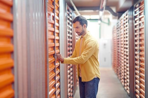 Vérification de la serrure. homme sérieux et attentif avec profil debout près de la porte de boxe au sous-sol touchant avec ses mains dans la serrure de la porte