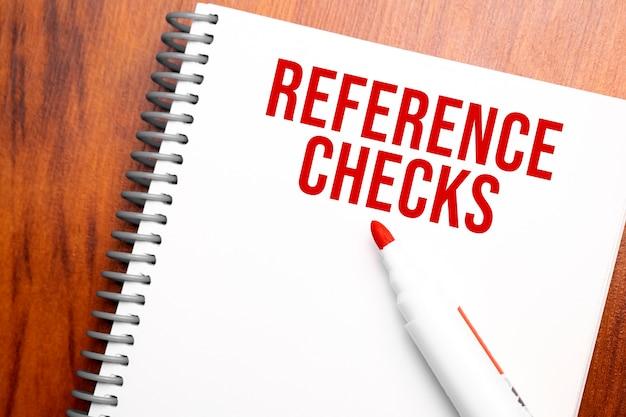 Vérifications de référence de texte écrites dans le bloc-notes, table en bois de bureau d'en haut, image conceptuelle pour le titre du blog ou l'image d'en-tête. aspect de couleur vintage vieilli.