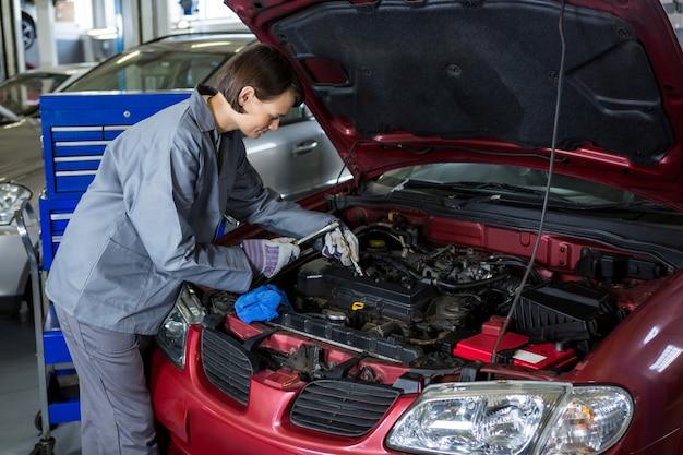 Vérifier le niveau d'huile dans un moteur de voiture mécanicien femme