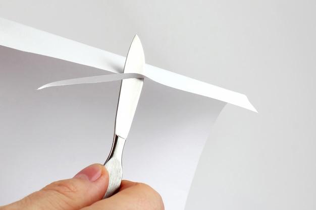 Vérifiez l'affûtage des lames de scalpel médical sur papier. outils de traitement