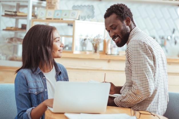 Vérifiez-le. femme charmante souriante montrant à son collègue masculin la présentation de leur projet, attendant son avis pendant que l'homme le regarde et prend des notes