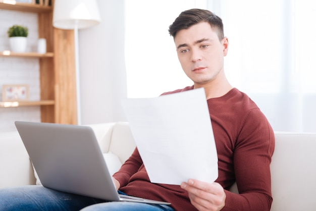 Vérifiez toujours. confiant étudiant masculin agréable tenant du papier tout en utilisant un ordinateur portable