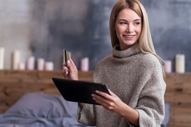 Vérifiez vos paiements. jolie jeune femme détendue à l'aide de tablette et de carte de crédit tout en payant les factures et en restant à la maison.