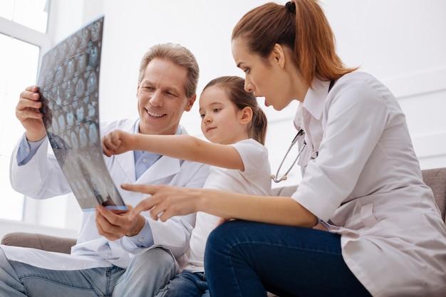 Vérifions-le ensemble. des chirurgiens éminents et compétents sages regardant à travers une scintigraphie cérébrale et apprenant de nouvelles choses ensemble pendant que la fille leur rend visite régulièrement