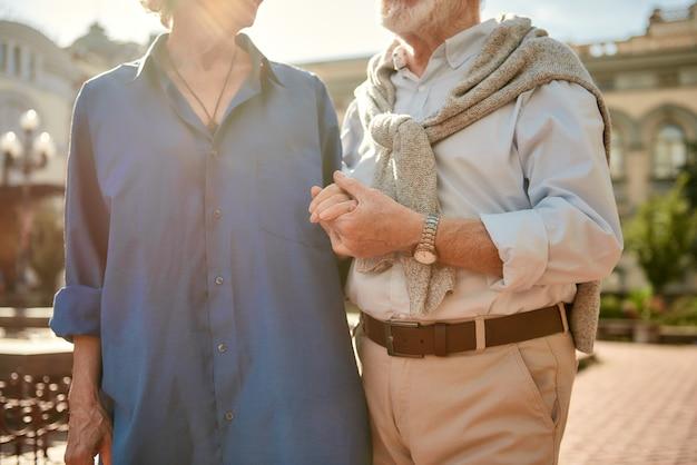 Le véritable amour ne meurt jamais photo recadrée d'un couple de personnes âgées se tenant la main tout en se tenant ensemble à l'extérieur