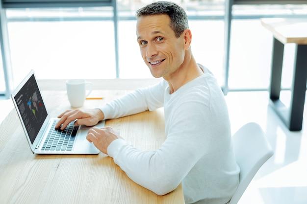 Véritable bourreau de travail. bel homme intelligent positif étant dans son bureau et se concentrant sur le travail tout en faisant son travail