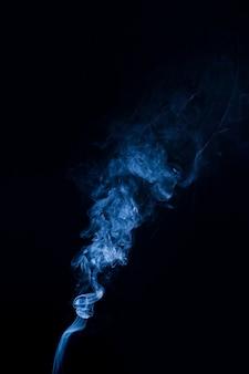 Véritable fumée bleue bouillonnant sur fond noir