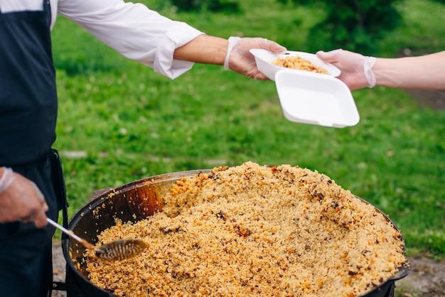 Véritable pilaf ouzbek dans un immense chaudron. cuisiner des plats nationaux.