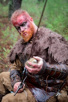 Véritable viking affilant son épée avec une pierre