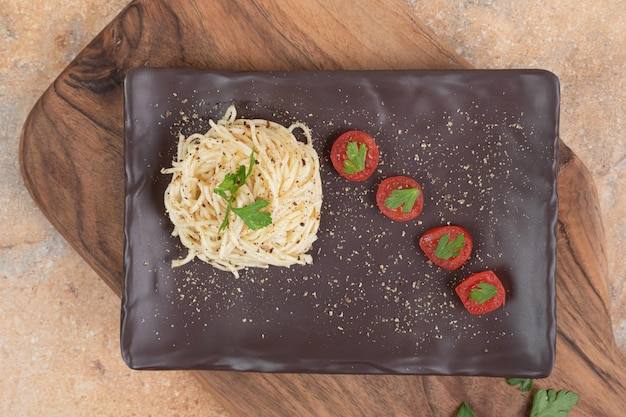 Vermicelles aux épices et tomates sur plaque noire.