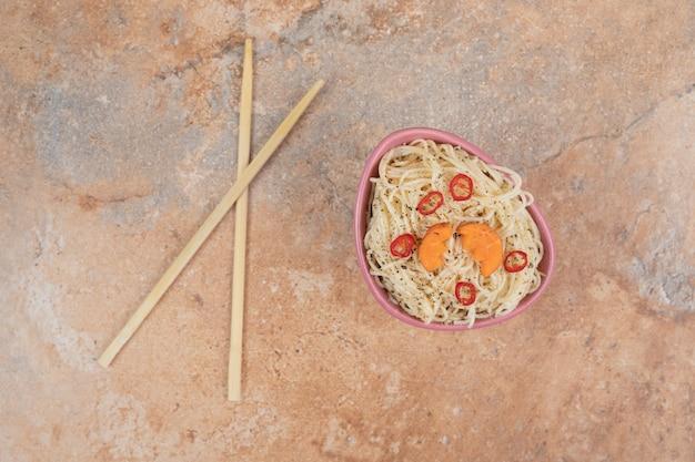 Vermicelles aux épices et tranches de poivre sur fond orange
