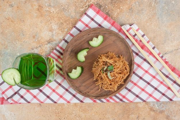 Vermicelles frits avec des tranches de concombre sur une plaque en bois et un verre de jus