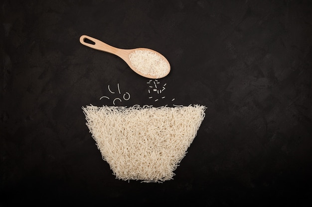Vermicelles ou nouilles chinoises à la farine de riz disposées sur fond texturé sombre en forme de bol