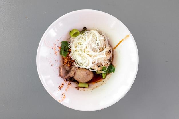 Vermicelles secs de nouilles thaïlandaises avec des porcs dans un petit bol blanc.