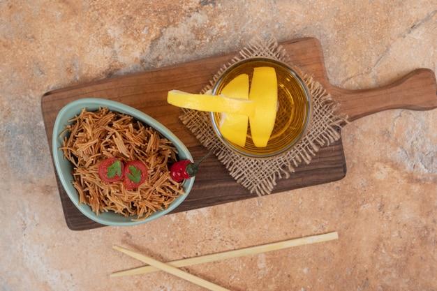 Vermicelles à la tomate et verre de jus sur planche de bois