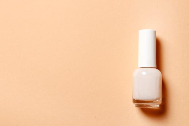 Vernis à ongles beige sur fond rose avec place pour le texte. français