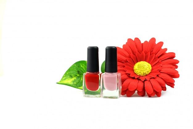 Vernis à ongles cosmétique rouge et rose avec des fleurs sur fond blanc