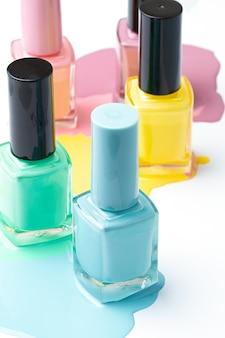 Vernis à ongles couleur pastel renversé isolé sur fond blanc.