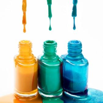 Vernis à ongles dégoulinant de pinceau en bouteille sur fond blanc