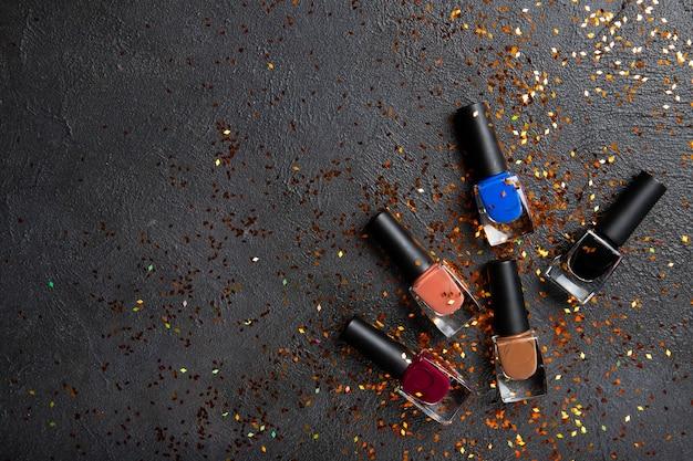 Vernis à ongles sur un mur noir. vernis à ongles colorés. place pour le texte