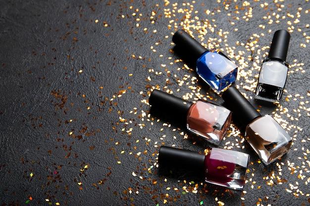 Vernis à ongles sur un mur noir. vernis à ongles colorés