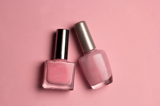 Vernis à ongles rose vue de dessus sur fond rose