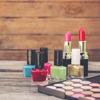 Vernis à ongles, rouge à lèvres, perles sur vieux bois