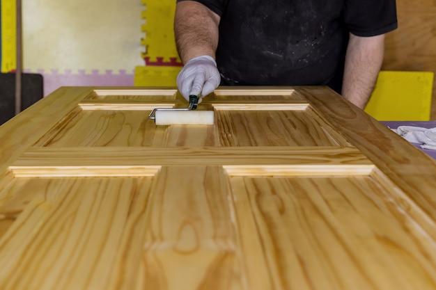 Vernis de peintre entrepreneur pour peindre une nouvelle porte d'entrée en bois à l'aide de vernis à rouleau à main avec des gants