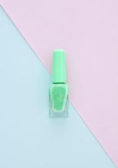Vernis vert clair sur papier vierge de couleur bleue, espace pour le design, concept beauté.