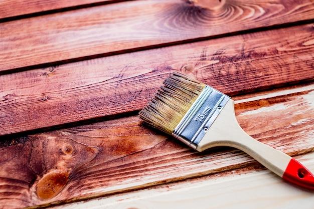 Vernissage d'une étagère en bois avec un pinceau.