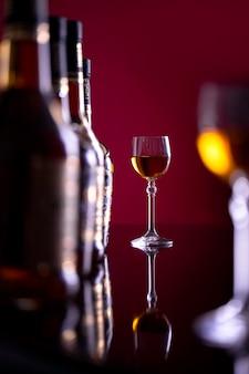 Un verre avec de l'alcool sur un fond bordeaux à côté de bouteilles en verre