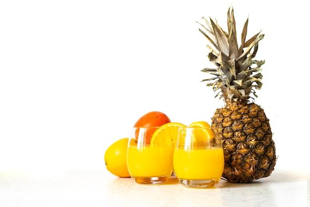 Verre d'ananas frais et smoothie orange sur table en bois isolé b