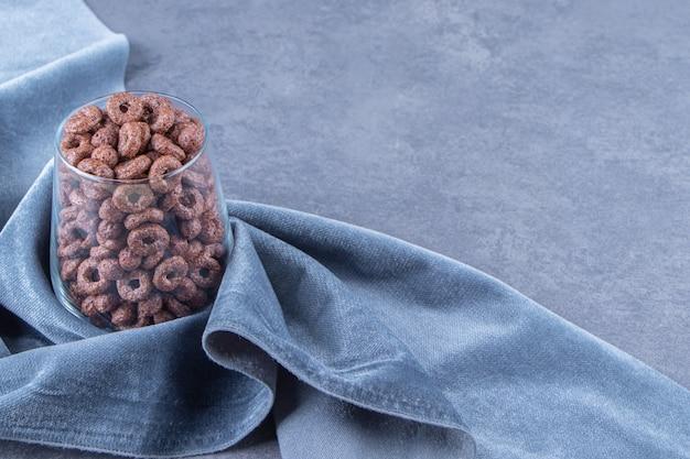 Un verre d'anneaux de maïs sur un morceau de tissu, sur le fond bleu.
