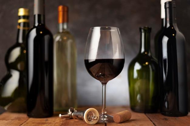 Verre avec arrangement de bouteilles de vin derrière