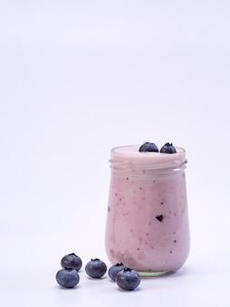 Verre au yaourt aux myrtilles fraîches sur fond blanc