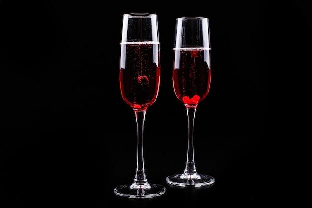 Verre avec des baies et des cocktails rouges alcool champagne sur fond noir
