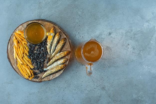 Un verre de bière et des amuse-gueules à bord et une carafe de bière, sur la table bleue.