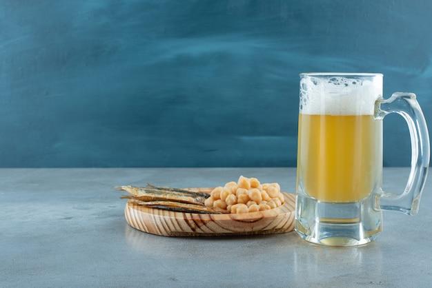 Un verre de bière avec une assiette en bois de poisson et de petits pois. photo de haute qualité