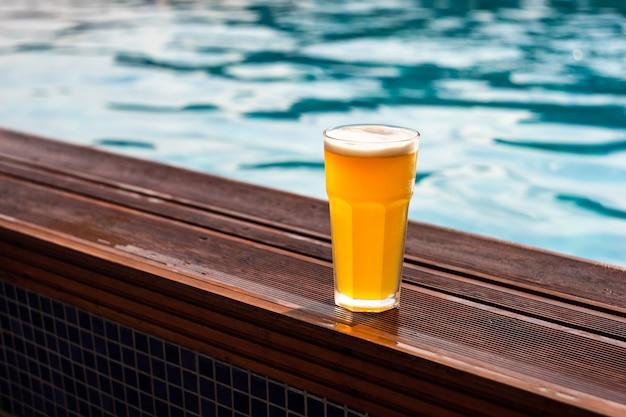 Verre de bière au bord de la piscine