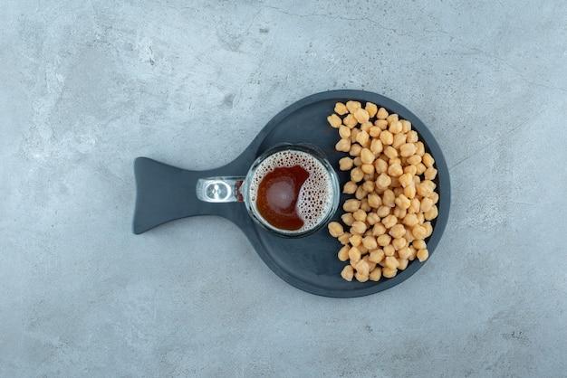 Un verre de bière aux petits pois sur une planche à découper sombre. photo de haute qualité