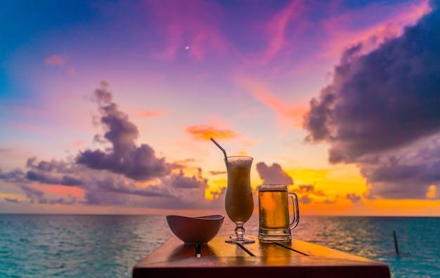 Un verre de bière avec une belle île des maldives tropicales.