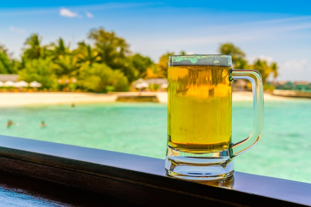Un verre de bière avec la belle île tropicale des maldives.