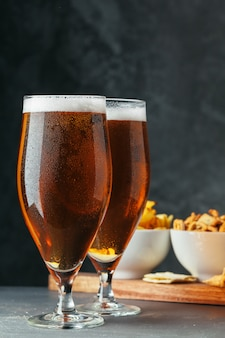 Verre de bière blonde avec des bols à collation