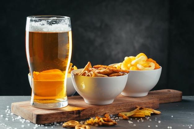 Verre de bière blonde avec bols à snacker sur pierre sombre