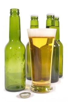 Verre de bière blonde avec des bouteilles vertes