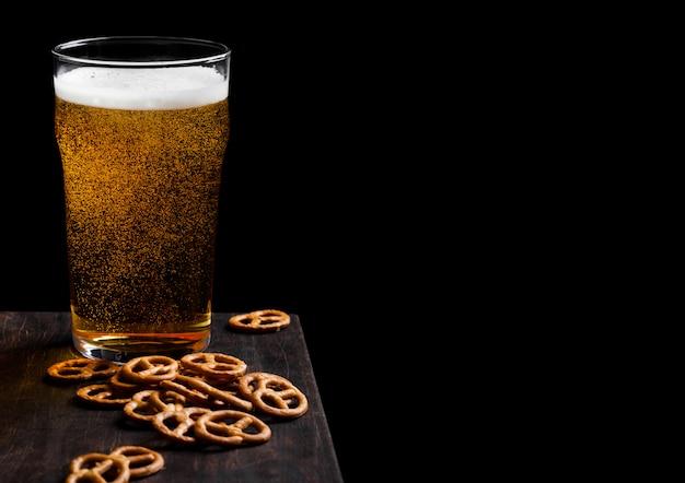 Verre de bière blonde avec des collations de bretzel sur planche de bois vintage sur fond noir.