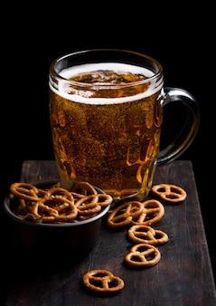 Verre de bière blonde avec des collations bretzel sur planche de bois vintage