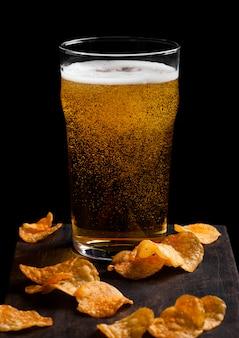 Verre de bière blonde avec des collations de chips de pommes de terre sur planche de bois vintage