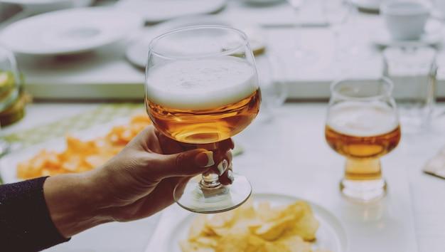 Verre de bière blonde dans les mains