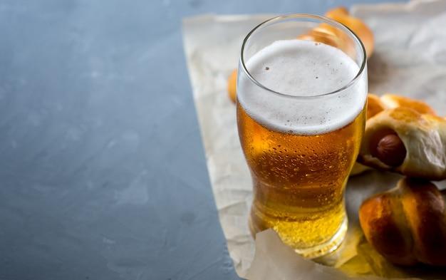 Un verre de bière blonde légère et saucisse sur une table en béton copy space
